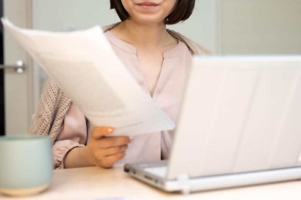 在宅勤務をしている書類をチェックする女性